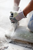 Man sawing with grinder detail. Man's hands in gloves sawing stone with grinder Royalty Free Stock Photography