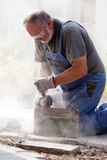 Man sawing with grinder. Hard working bearded man with safety glasses, blue workwear and gloves sawing stone with grinder Stock Photography