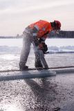 A man sawing ice with a chainsaw at a frozen lake in Savonlinna, Finland Stock Photos