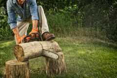Man sawing a log. In his back yard Royalty Free Stock Photography