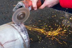 Man sawing metal pipe with Angle grinder royalty free stock photography