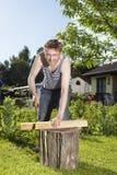 Man sawing piece of wood. En tree trunk in back garden Stock Images