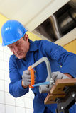 Man sawing a pipe. Royalty Free Stock Image
