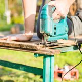 Man sawing plank in park Royalty Free Stock Photography