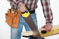 Man sawing plank of wood Stock Image