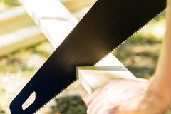 Man sawing a wood board outdoors Stock Images