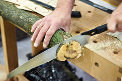 Man sawing wood handsaw. On a carpentry table Stock Image