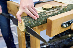 Man sawing wood handsaw on carpentry table Stock Images