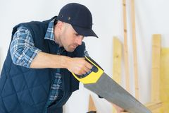 Man sawing wood handsaw on carpentry table. Man sawing wood handsaw on a carpentry table Royalty Free Stock Photo