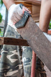 A man is sawing wood rod. Close up a man is sawing wood rod stock images