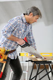 Man sawing wood working on home improvement Royalty Free Stock Image
