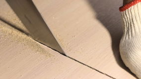 Man sawing wooden board with hand saw stock footage