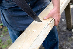 A man sawing a wooden board with a handsaw. A man sawing a board with a handsaw Royalty Free Stock Photos