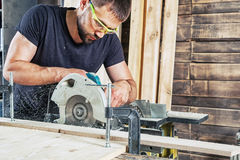 Man sawing wooden with a modern circular saw royalty free stock photography