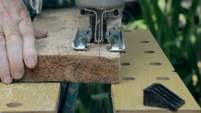 Man sawn a wooden board with an electric jigsaw. stock video