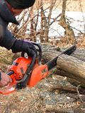A man saws a branch of locust tree with an orange chain saw for gasoline to clean garden or park. stock photos