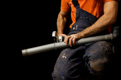 Man saws grinder plastic pipe.  on black background. Royalty Free Stock Photos