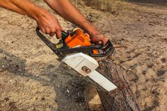 A man saws a log with a chainsaw. The man saws the log with a black-orange-white chain saw, against the background of sand. a man saws a log with a chainsaw royalty free stock images