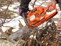 Man saws tree with an orange chain saw Husqvarna for gasoline to clean the old overgrown fence. royalty free stock image