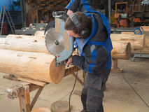 Man saws wood logs with a chainsaw Royalty Free Stock Photography