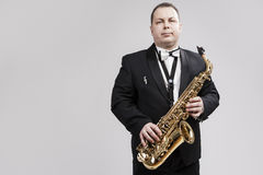 Man with Saxophone in Suite Posing Against White Background Royalty Free Stock Photo