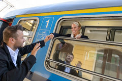 Man saying goodbye to woman on train. Man saying goodbye to women on train smiling window commuter Royalty Free Stock Images