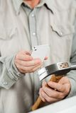 Man Scanning Hammer Through Smartphone. Midsection of mature man scanning hammer through smartphone in hardware store Royalty Free Stock Photos