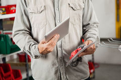 Man Scanning Product Through Digital Tablet. Midsection of man scanning product through digital tablet in hardware store Royalty Free Stock Photos
