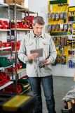 Man Scanning Product Through Tablet Computer. Mature man scanning product through tablet computer in hardware store Stock Photos
