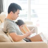 Man scanning QR code. With smart phone. Asian family at home, living lifestyle indoors royalty free stock photo