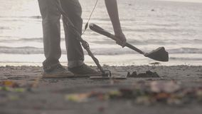 Man is scanning sand on beach by metal detector and starting to dig on the coastline. Legs close-up, side view stock footage