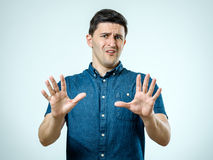 Man with scared expression on his face making frightened gesture. With his palms as if trying to defend himself from someone stock photos