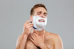 Man scares to shave over gray background Stock Photography