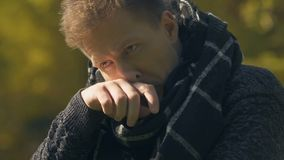 Man in scarf coughing outdoor, getting sick with flu on cold weather, closeup