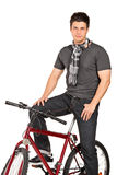 Man with scarf posing seated on a bicycle Stock Image