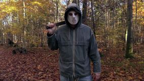 Man with scary Halloween mask look into the camera and walking away. In autumn day stock footage