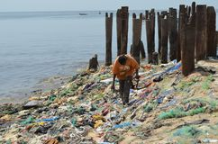 A beach covered by plastic litter in the Petite Côte of Senegal, Western Africa. A man scavenges amongst the plastic litter in a beach on Senegal`s Petite C stock photo