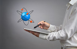 Man scientist holding a tablet PC with atom model, research concept Royalty Free Stock Image