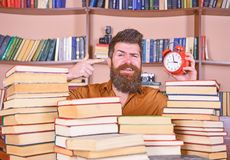 Man, scientist peeking out of piles of books with alarm clock. Teacher or student with beard studying in library. Man on. Happy face pointing at clock stock photos