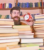 Man, scientist peeking out of piles of books with alarm clock. Teacher or student with beard studying in library. Time. Flow concept. Man on happy face looking royalty free stock photos