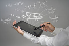 Man scientist or student holding tablet PC and working with various high school maths and science formulas. Stock Photo