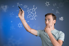 Man scientist with stylus or pen working with chemical formulas on blue background. Stock Photos