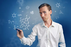 Man scientist with stylus or pen working with chemical formulas on blue background. Stock Photo