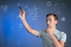 Man scientist with stylus or pen working with chemical formulas on blue background. Young man scientist with stylus or pen working with chemical formulas on Stock Images