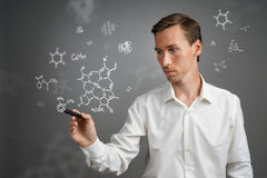 Man scientist with stylus or pen working with chemical formulas on gray background. Young man scientist with stylus or pen working with chemical formulas on Royalty Free Stock Image