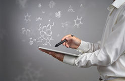 Man scientist with tablet pc and stylus or pen working with chemical formulas on gray background. Royalty Free Stock Images