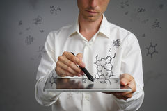 Man scientist with tablet pc and stylus or pen working with chemical formulas on gray background. Stock Photography