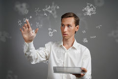 Man scientist with tablet pc working with chemical formulas on gray background. Royalty Free Stock Photography