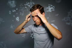 Man scientist thinking about chemical formulas on gray background. Young man scientist thinking about chemical formulas on gray background Royalty Free Stock Images