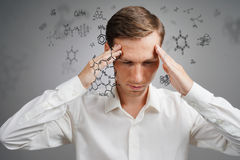 Man scientist in white shirt thinking about chemical formulas on gray background. Stock Photo